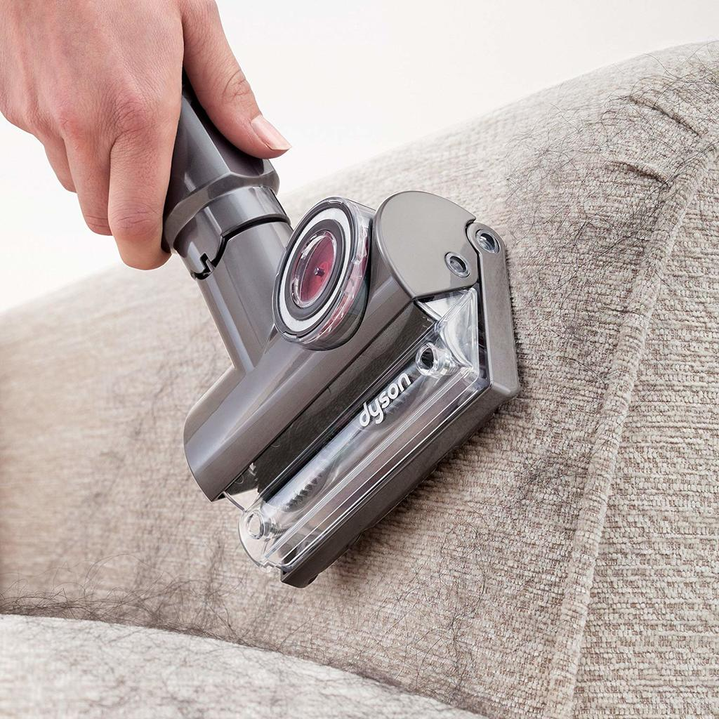 person cleaning the seat using handheld vacuum