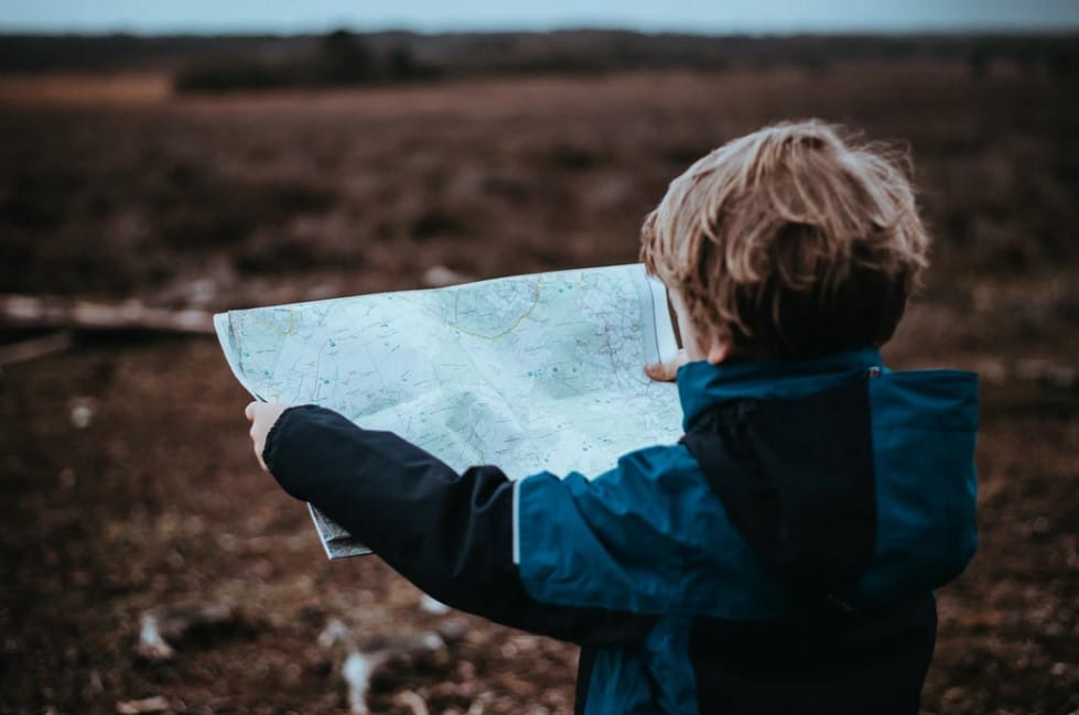 kid reading a map for a road trip