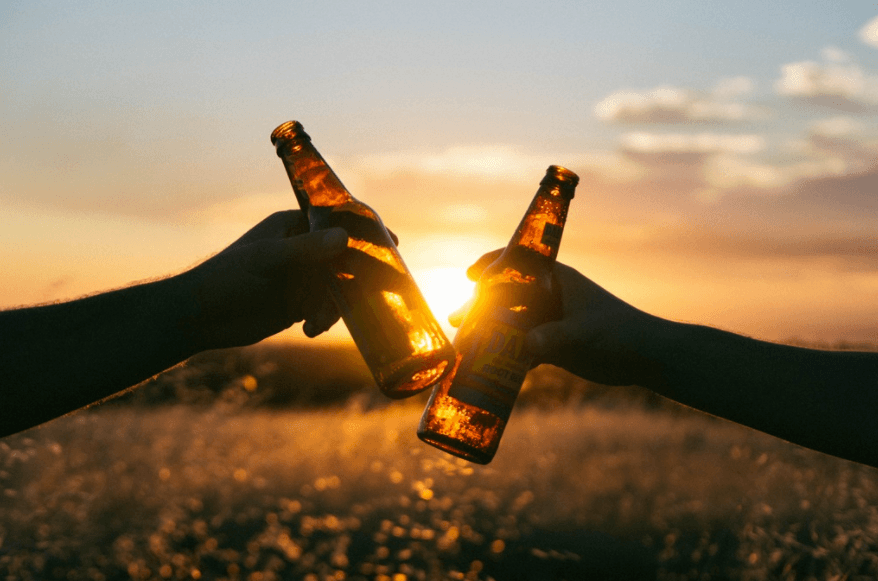 toast of cold beer at sunset