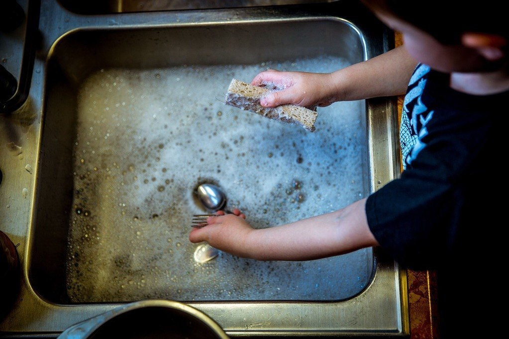 child washing spoons on clogged sink
