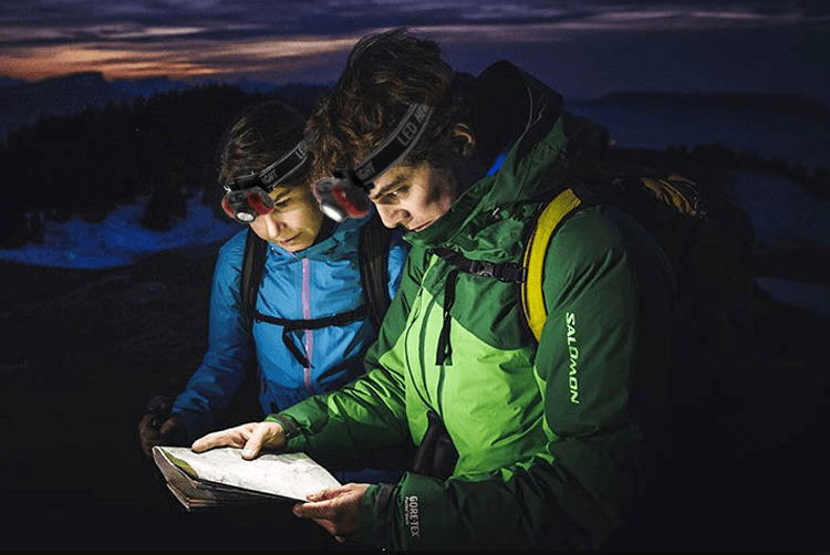 Camper couples reading a map while it's evening