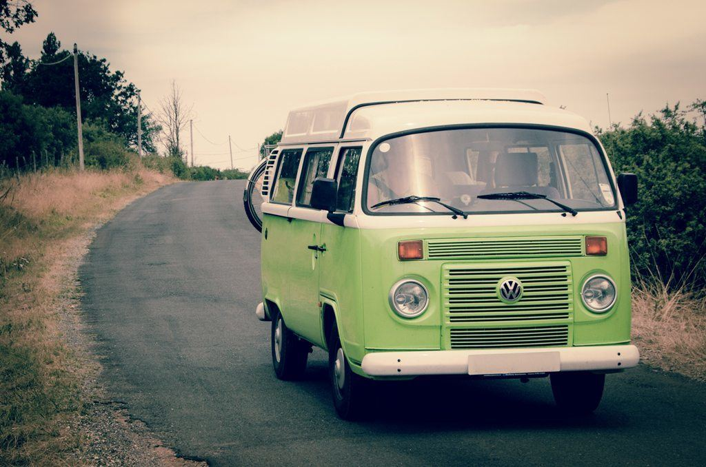 Green and white recreational vehicle on the road