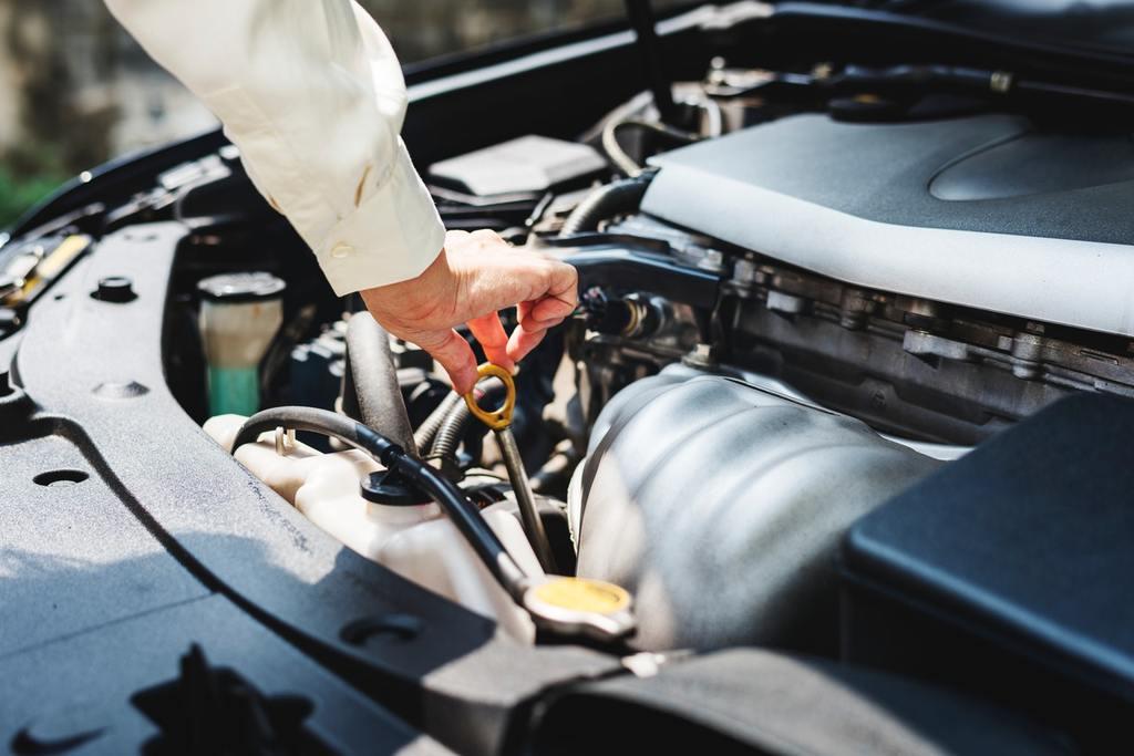 hand tinkering car engine