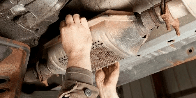 man fixing the catalytic converter of a car