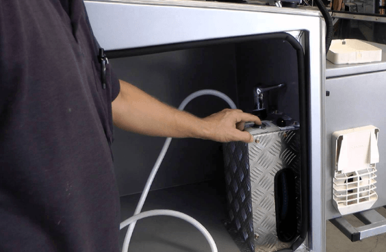 man holding the best tankless water heater for rv