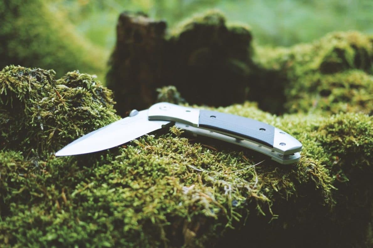 survival knife semi folded and placed on the mossy ground