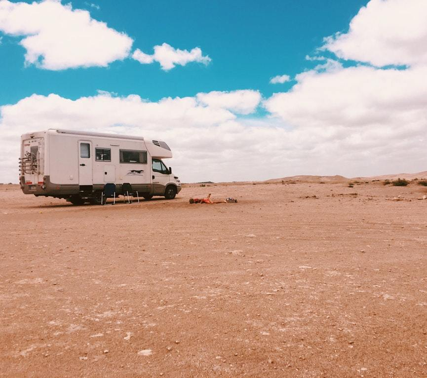 white RV parks on desert area under blue sky