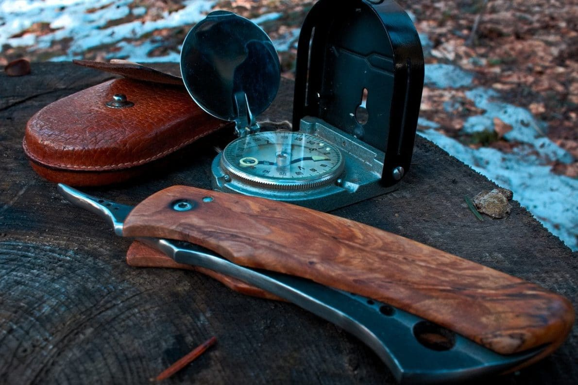 survival knife placed beside compass and leather pouch