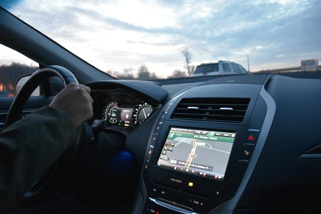 a man driving a car installed with the best double din head unit