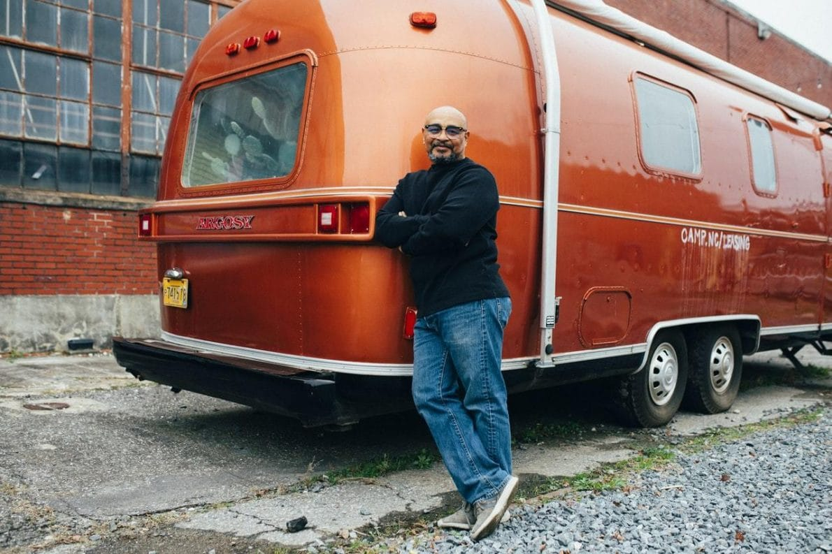 Man standing while leaning on orange camper