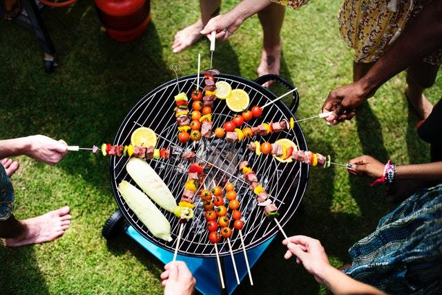 a group grilling skewered meat