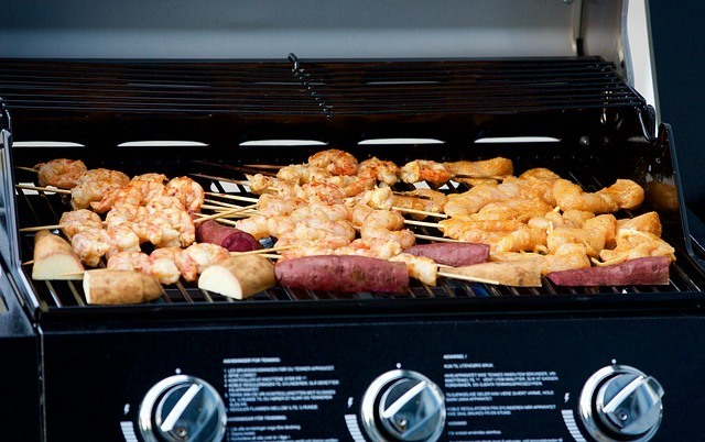 meat being cooked over grill with knobs