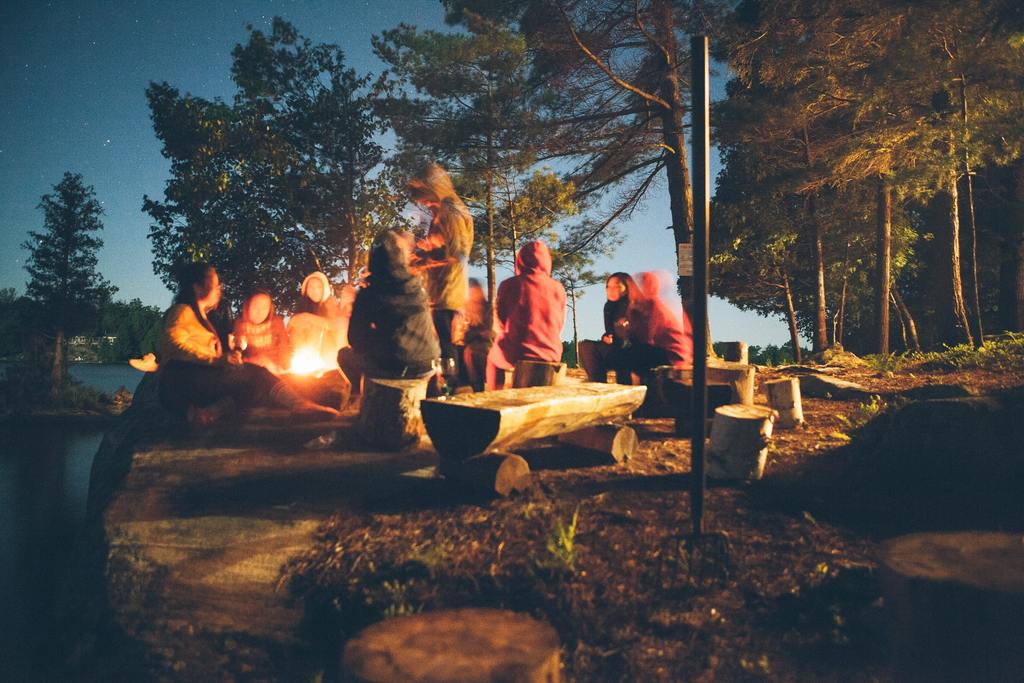 Campers around a campfire on a chilly autumn night
